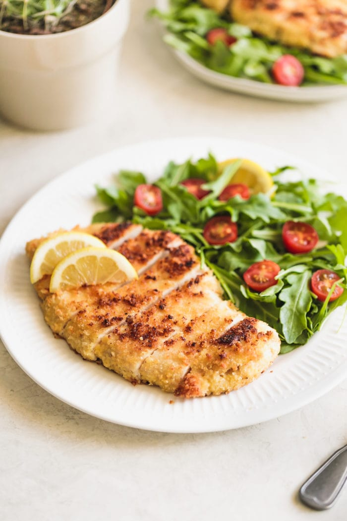 A white plate with crispy chicken milanese with salad and tomatoes ohsweetbasil.com