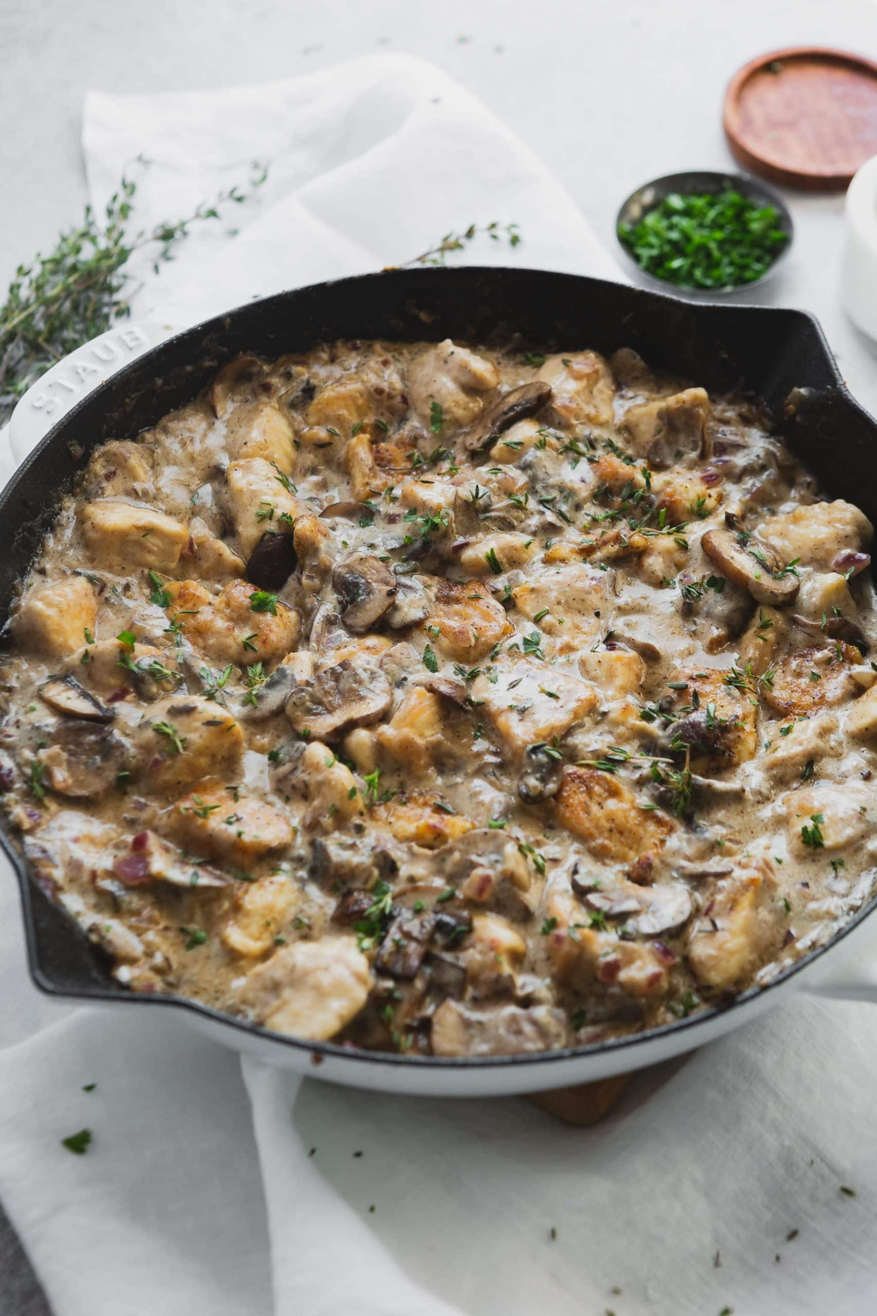 Chicken stroganoff in a Dutch Oven. The chunks of chicken are mixed in a creamy sauce with mushrooms and herbs.