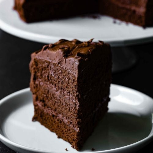 A slice of three-layered chocolate cake with chocolate frosting. Chocolate frosting is spread between each layer and on the top and sides of the cake. There is a cake plate with chocolate cake in the background.