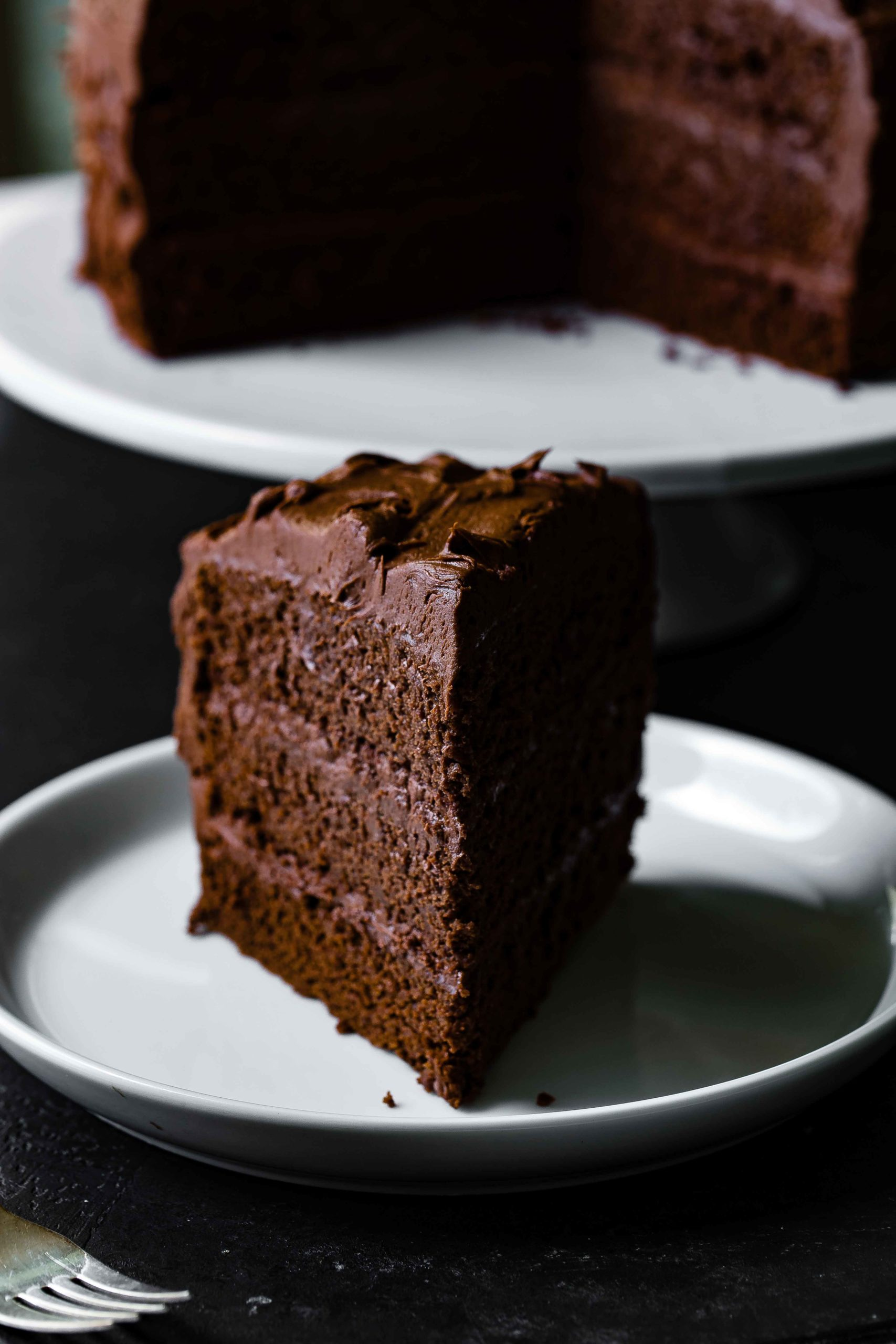 A slice of chocolate layer cake with chocolate frosting. Chocolate frosting is spread between each layer and on the top and sides of the cake. There is a cake plate with chocolate cake in the background.