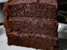 A big, tall slice of three layered chocolate cake with chocolate frosting. Each layer is frosted with thick chocolate frosting and the slice is sitting on a white dessert plate.