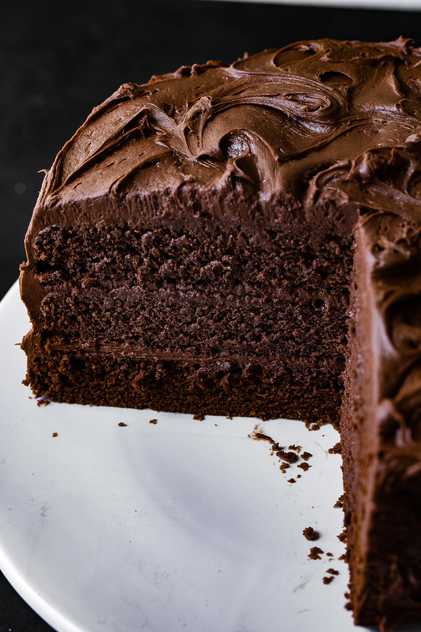 A chocolate layer cake with chocolate frosting. Several pieces have been cut from the cake exposing the moist, chocolaty inside. Each layer is frosted with the same creamy chocolate frosting that frosts the whole cake.