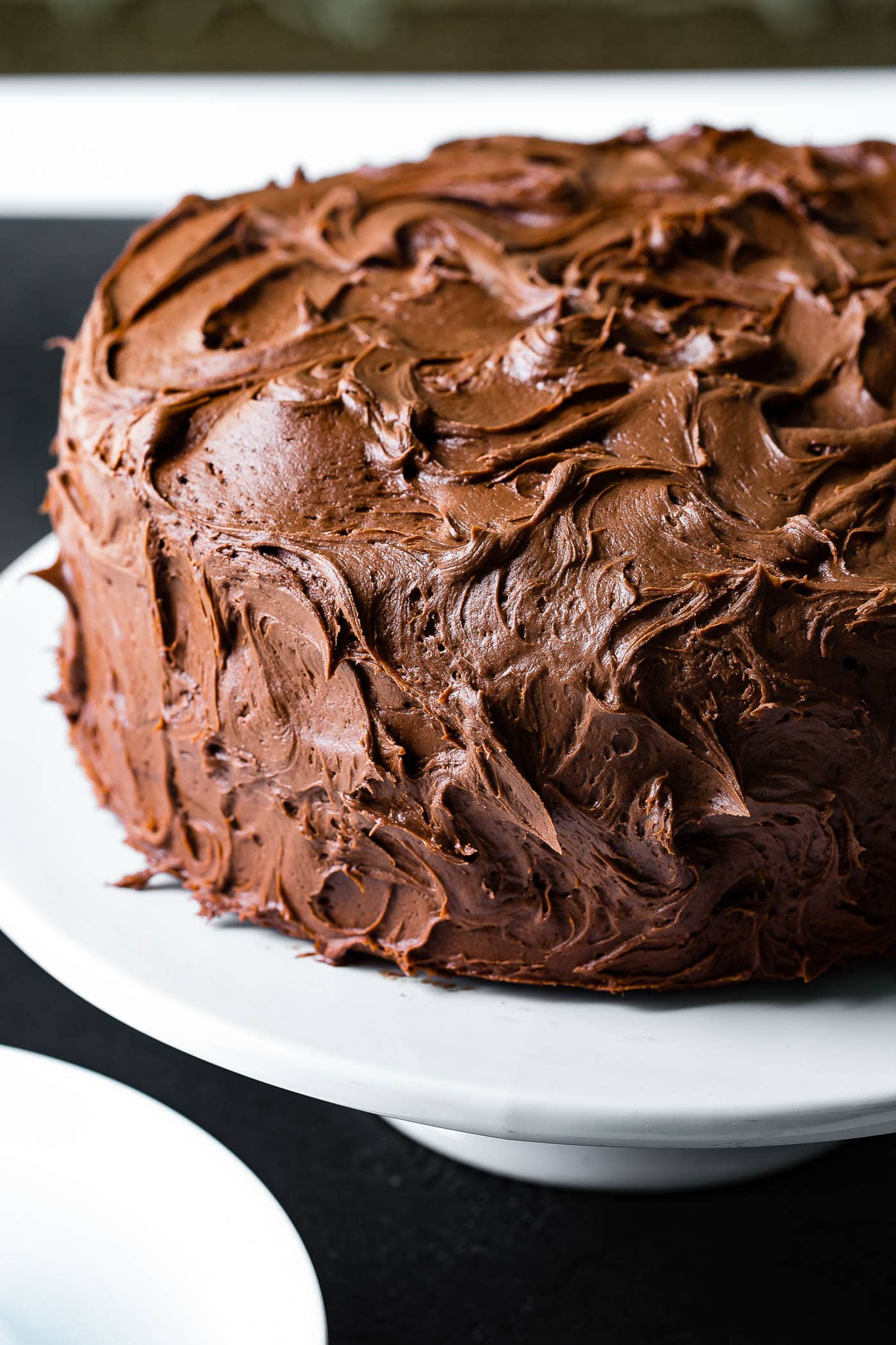 A whole moist chocolate cake with fluffy, dark chocolate frosting. The cake is on a white cake plate.