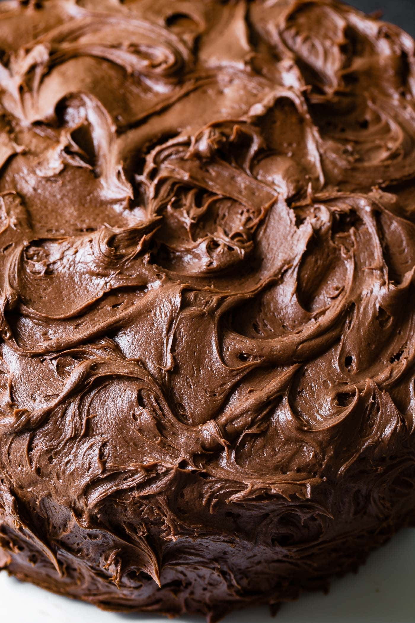 A close-up of the top of a moist chocolate cake that is frosted with beautiful chocolate frosting.