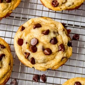 Baked chocolate chip cookies on a cooling rack.