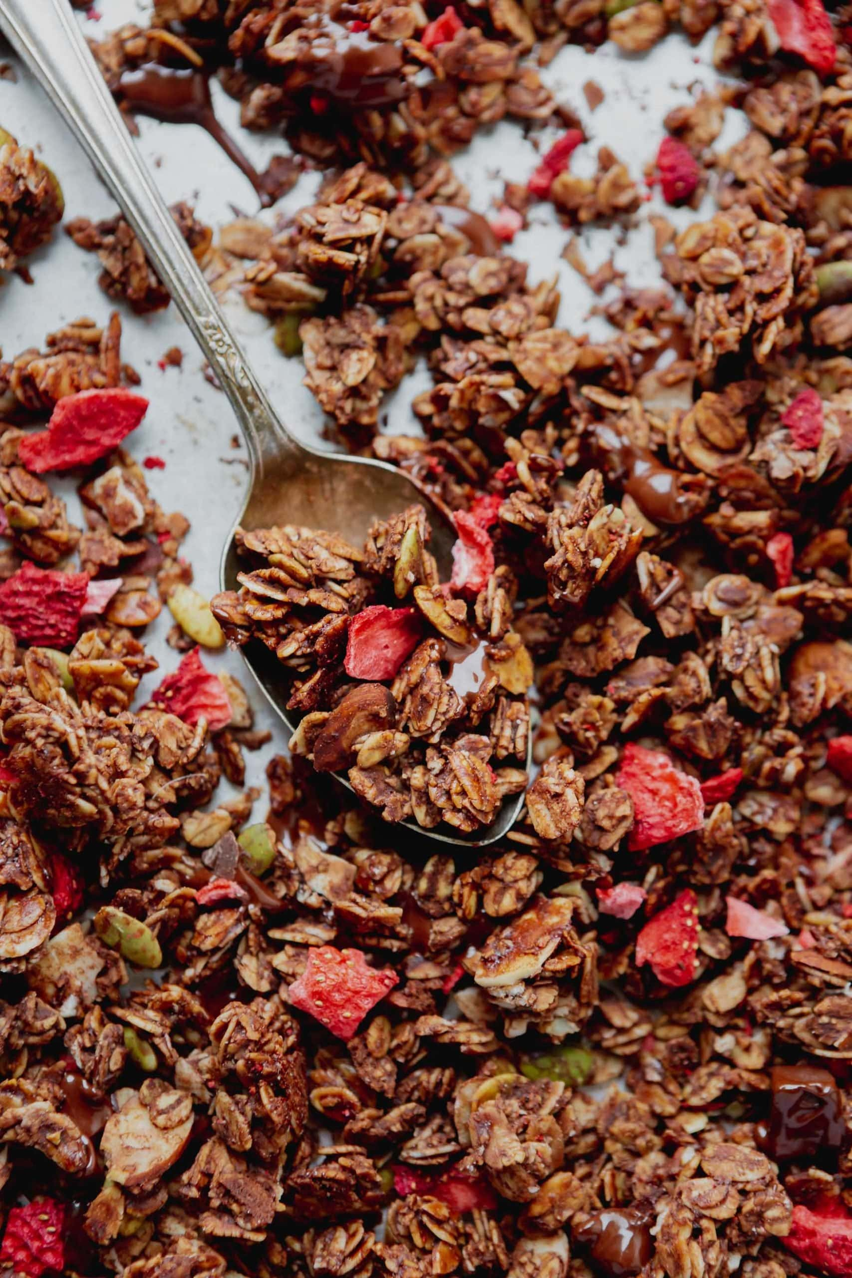 Chocolate granola with dehydrated strawberries on a baking pan with a spoon.