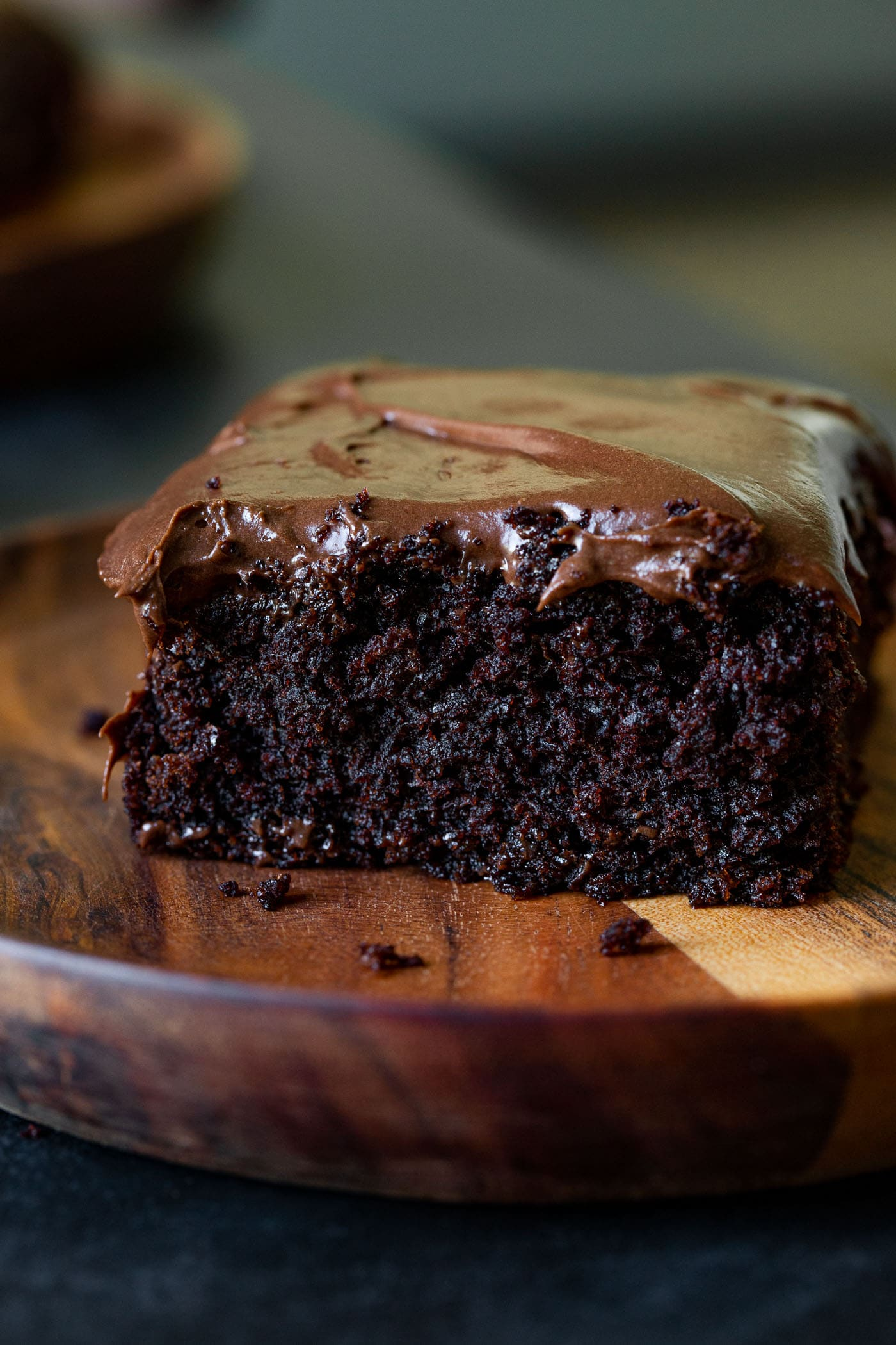 A slice of chocolate zucchini cake with creamy chocolate cream cheese frosting. The piece of cake is on a wooden dessert plate.
