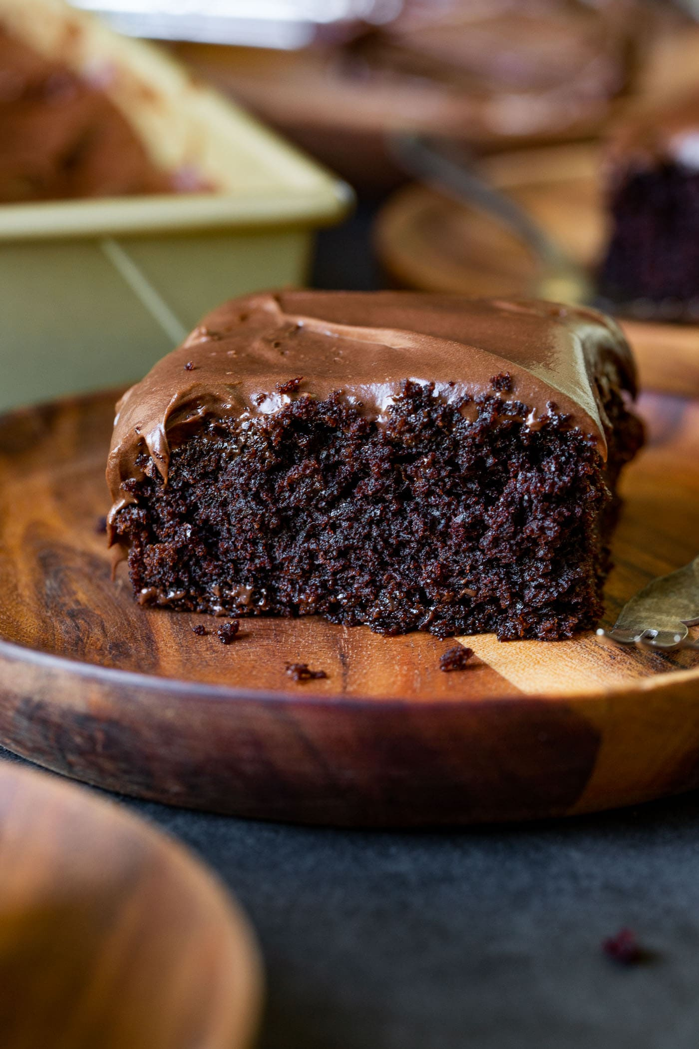 A slice of moist chocolate zucchini cake on a wooden dessert plate. The cake is frosted with chocolate cream cheese frosting.
