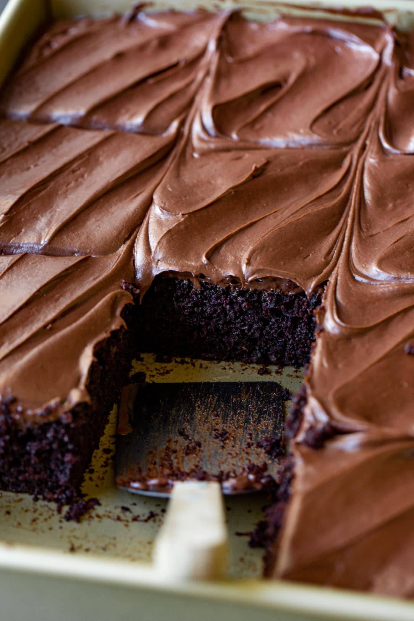 A pan of chocolate zucchini cake that has been cut into pieces and one piece has been removed. It is frosted with smooth, creamy chocolate frosting.