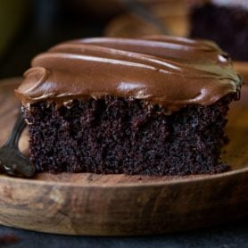 A slice of chocolate zucchini cake on a wooden dessert plate. The cake is frosted with creamy chocolate cream cheese frosting.