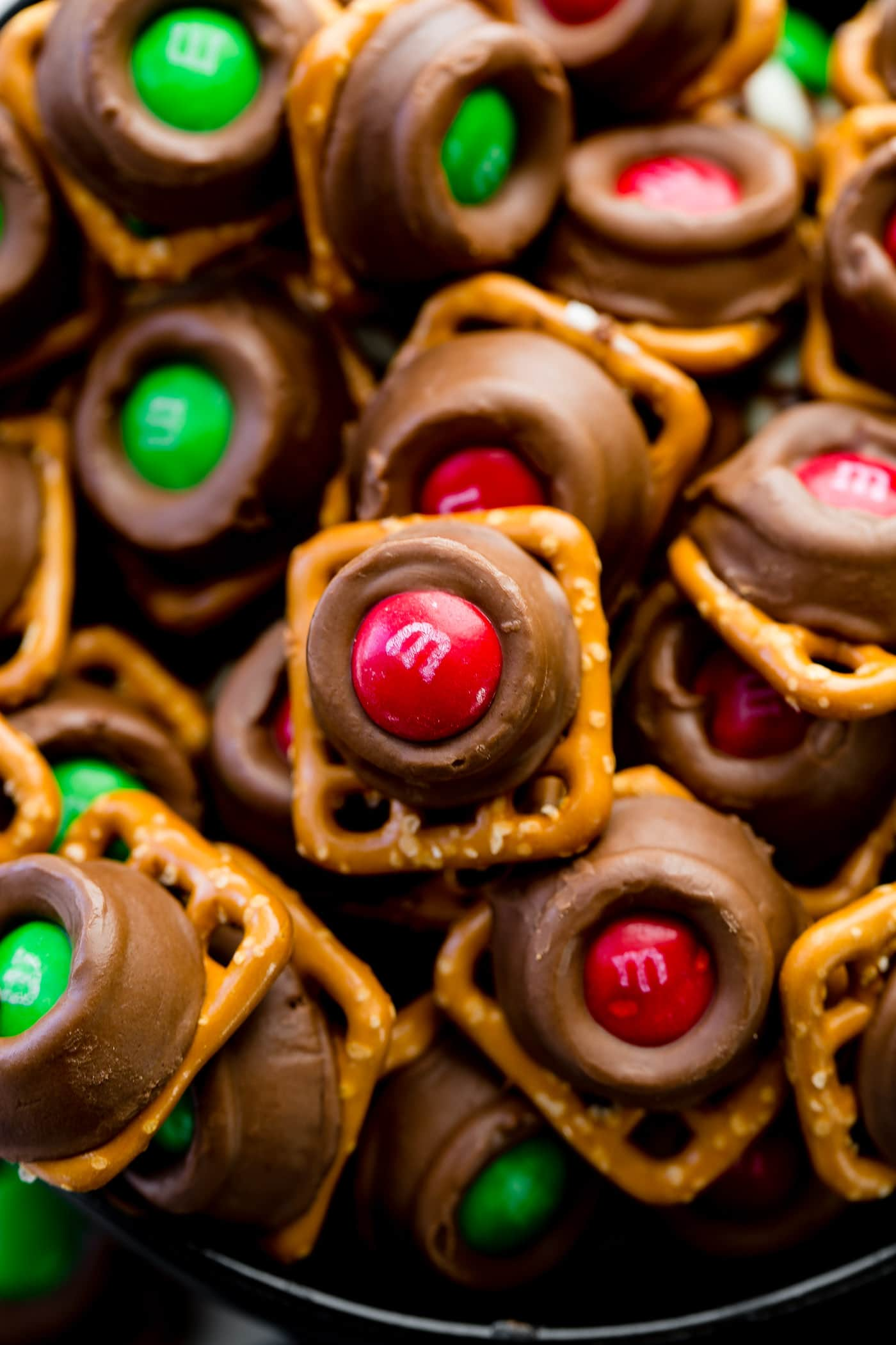a pile of square pretzels topped with rolos, milk chocolates filled with caramel and topped with christmas m&ms