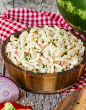 A wooden bowl on a red and white checkered napkin full of creamy macaroni salad.