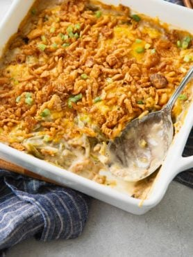 Green bean casserole that has been baked till the french fried onions on top are golden brown. You can see the green beans and sauce all mixed together with the onions on top.