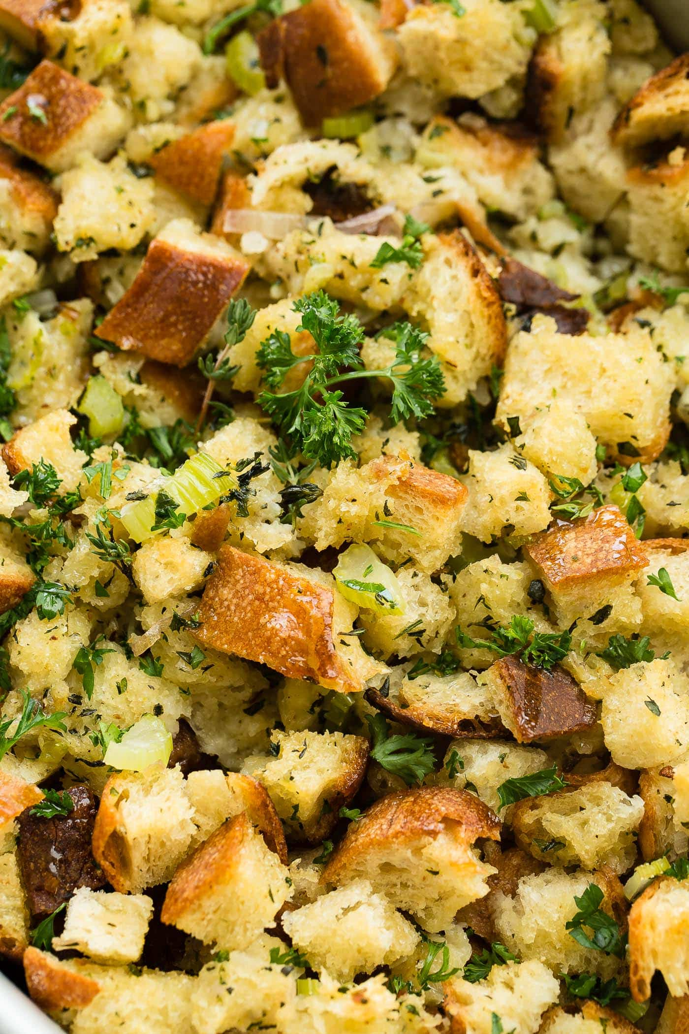 A close up photo of classic stuffing that is golden brown and topped with chopped fresh parsley.