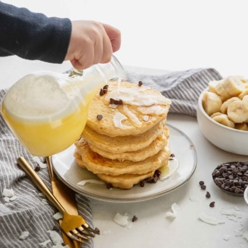 A stack of pancakes with coconut buttermilk syrup being poured over the top. The syrup is light yellow in color and there is a little white foam on top. there is a bowl of sliced bananas and a few chocolate chips around the pancakes.