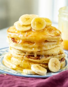 A photo of a blue and white plate with a stack of pancakes on it topped with banana slices and coconut buttermilk syrup.