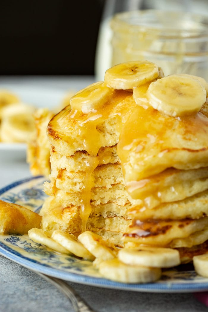 A photo of a blue and white plate with a stack of pancakes on it topped with banana slices and coconut buttermilk syrup with a slice of pancakes taken out.