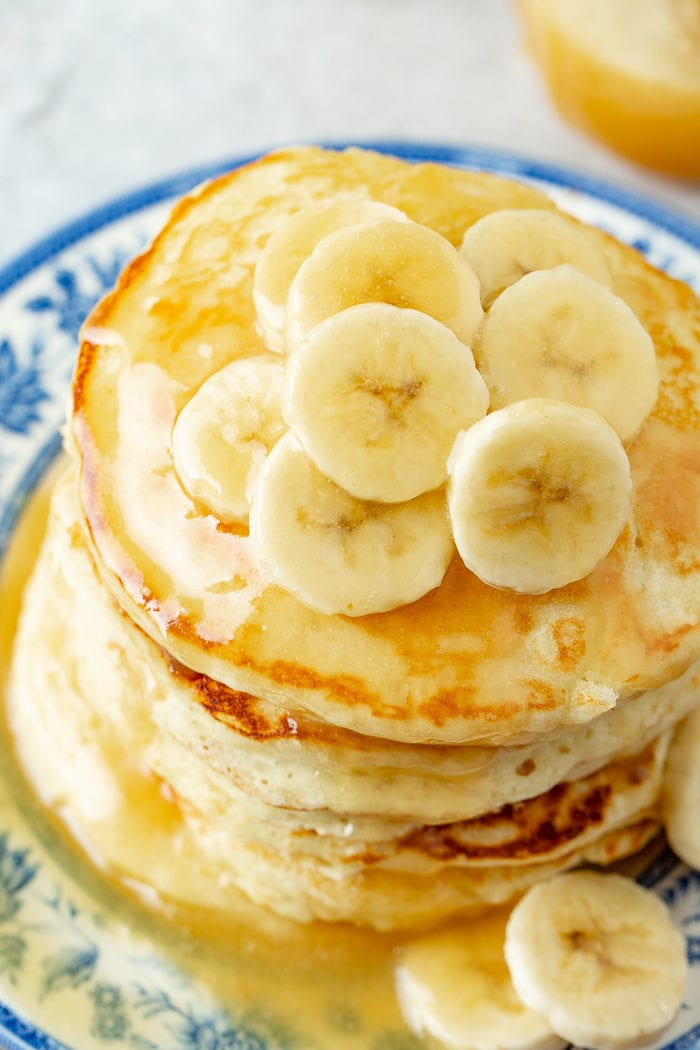 A photo taken from above of a blue and white plate with a stack of pancakes on it topped with banana slices and coconut buttermilk syrup.