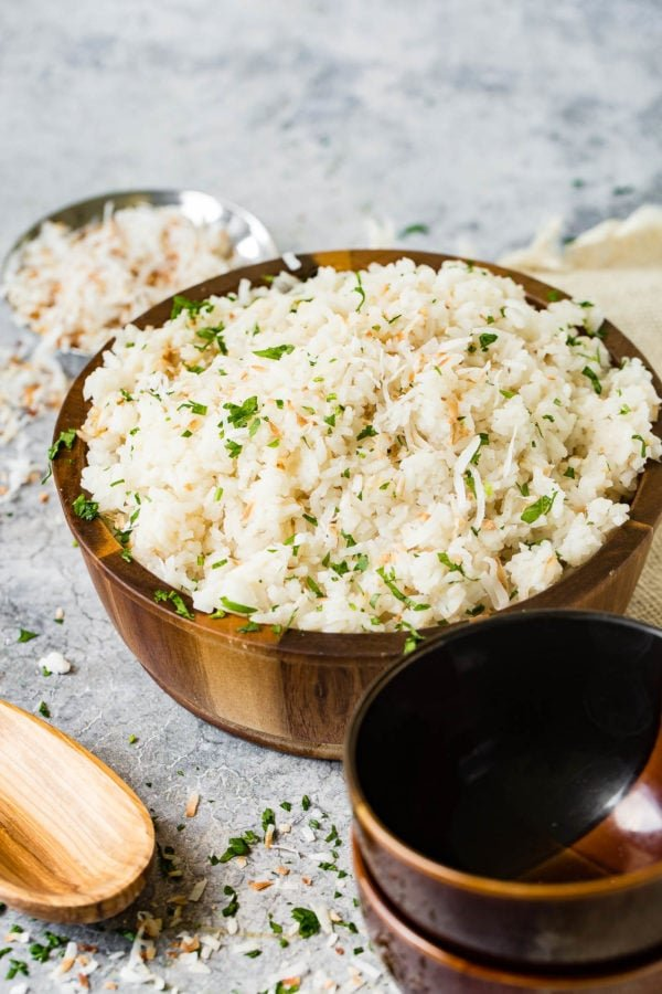 A photo of Brazilian coconut rice in a large wooden bowl and garnished with chopped fresh cilantro.