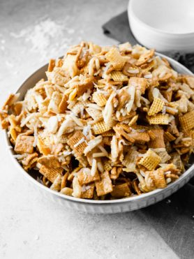 A bowl of coconut sweet chex mix. The mix has rice chex, corn chex and golden grahams with slivered almonds and shredded coconut mixed in.