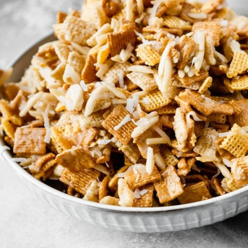 A large bowl containing coconut sweet chex mix. It is made of rice chex, corn chex and golden grahams. Slivered almonds and shredded coconut are mixed in with a sweet gooey syrup.