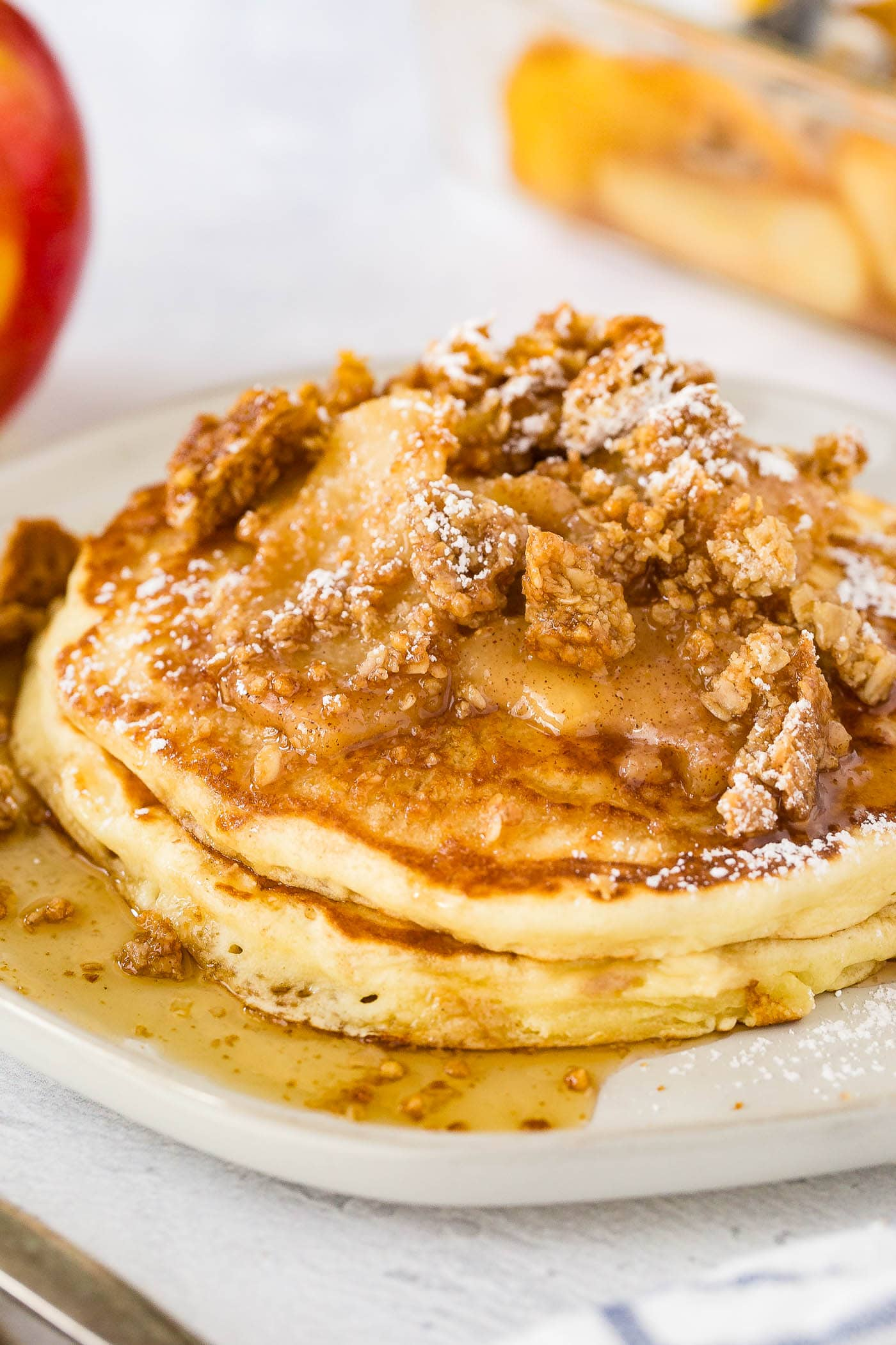 a plate stacked with fluffy pancakes topped with roasted apples, crumbled granola, powdered sugar and a drizzle of syrup with a side of bacon.