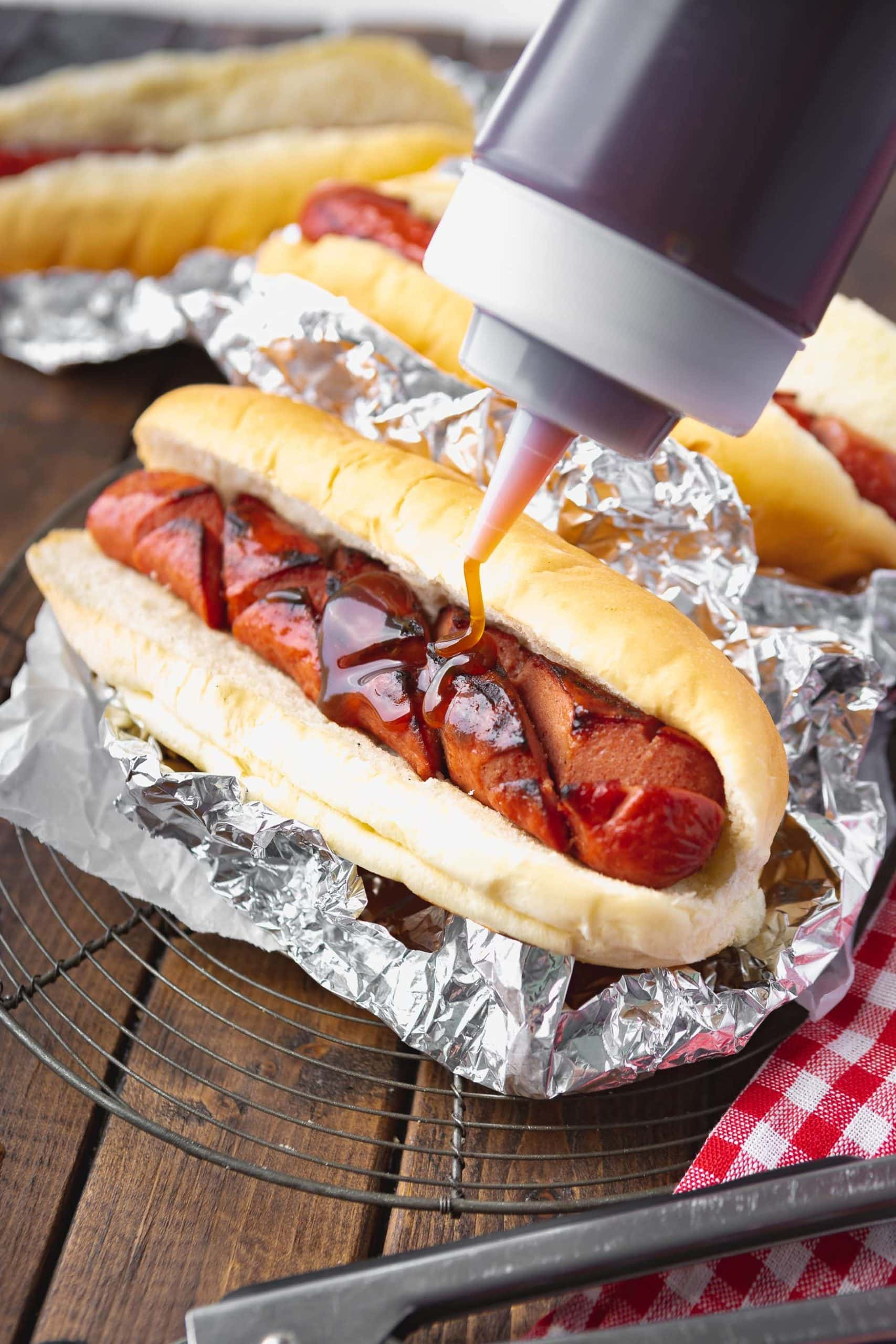 a photo of a grilled hotdog sitting in a bun inside of aluminum foil being drizzled with a sauce from a plastic bottle.