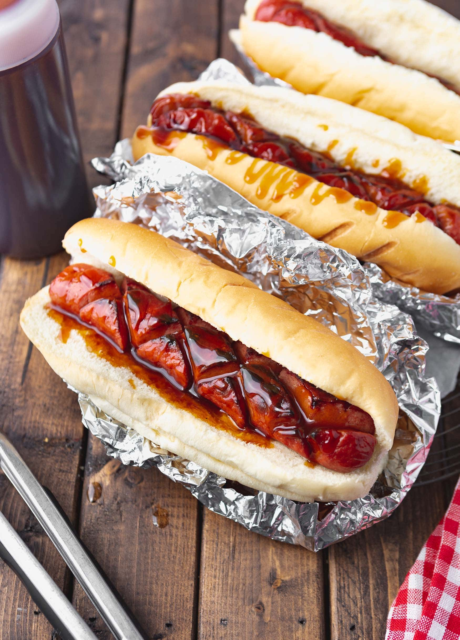 a photo of a grilled hotdog that has been sliced in a crisscross fashion sitting in a bun inside aluminum foil. The hotdog is covered in special sauce.