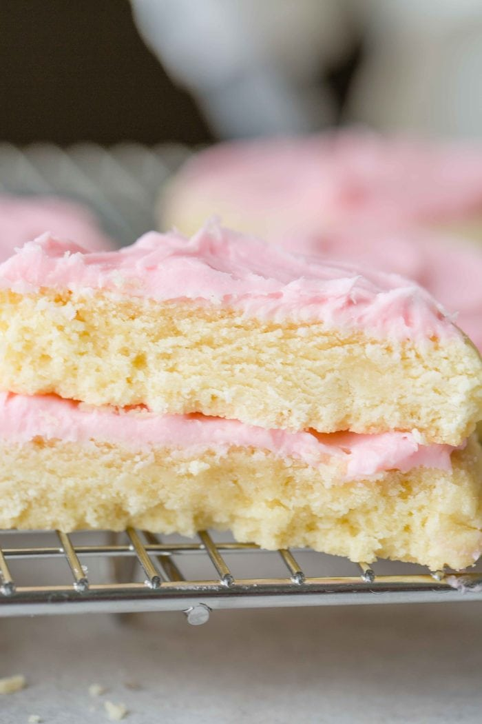 A photo of the cross section of two sugar cookies with pink frosting stacked on each other.
