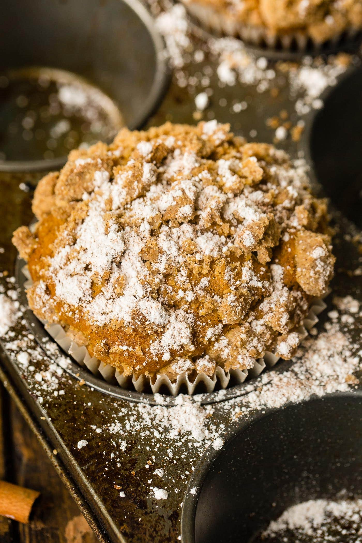 a jumbo pumpkin streusel muffin with a sprinkle of powdered sugar