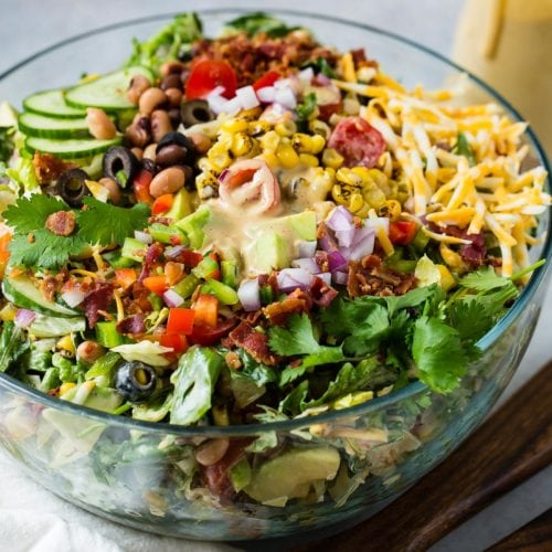 Cowboy salad in a glass serving bowl all ready to be served. It has sliced cucumbers, chopped lettuce, avocados, peppers, bacon, and olives and shredded cheese. It is topped with dressing. A container with extra dressing is in the background.