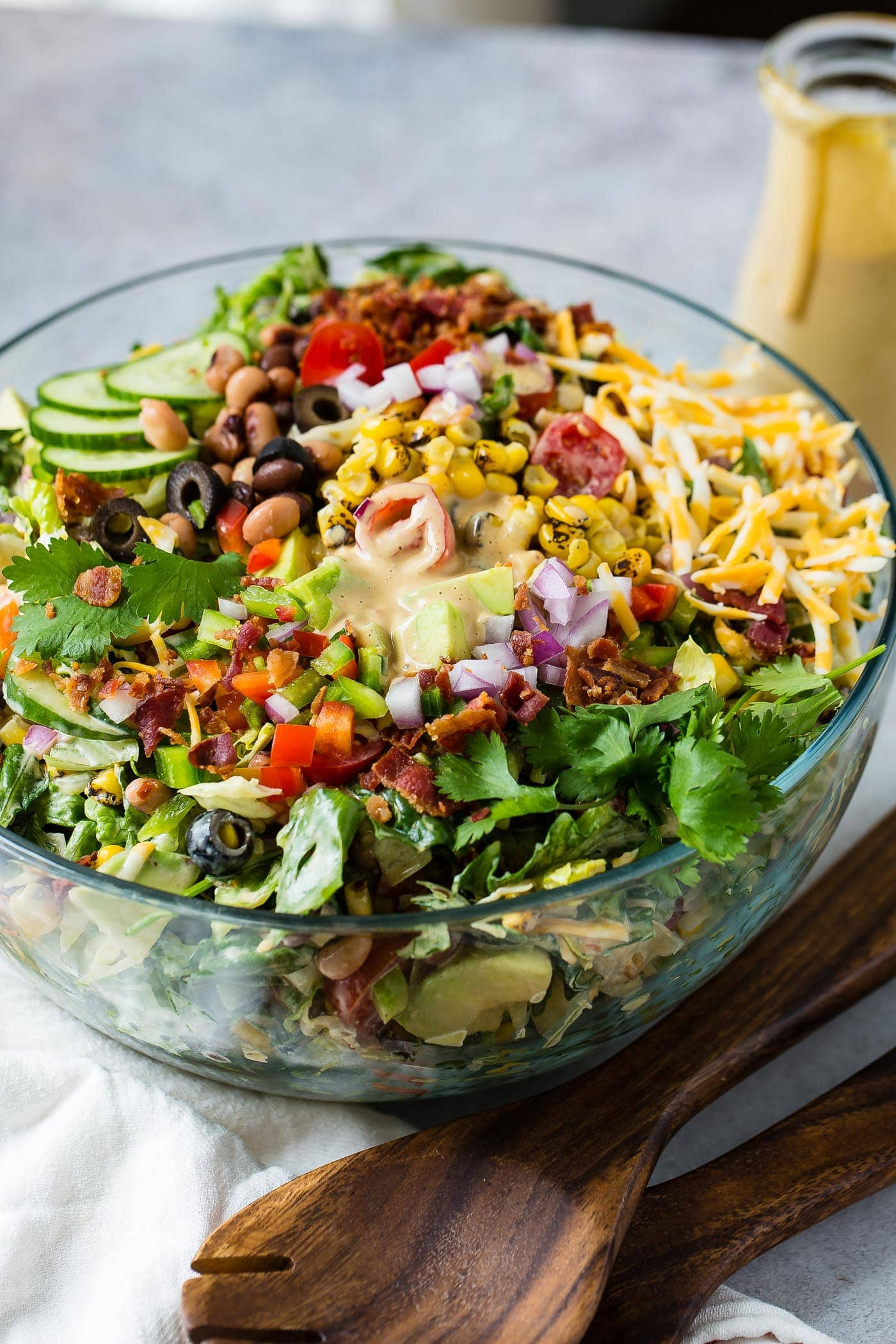 Cowboy salad in a glass serving bowl all ready to be served. It has sliced cucumbers, chopped lettuce, avocados, peppers, bacon, and olives and shredded cheese. It is topped with dressing.