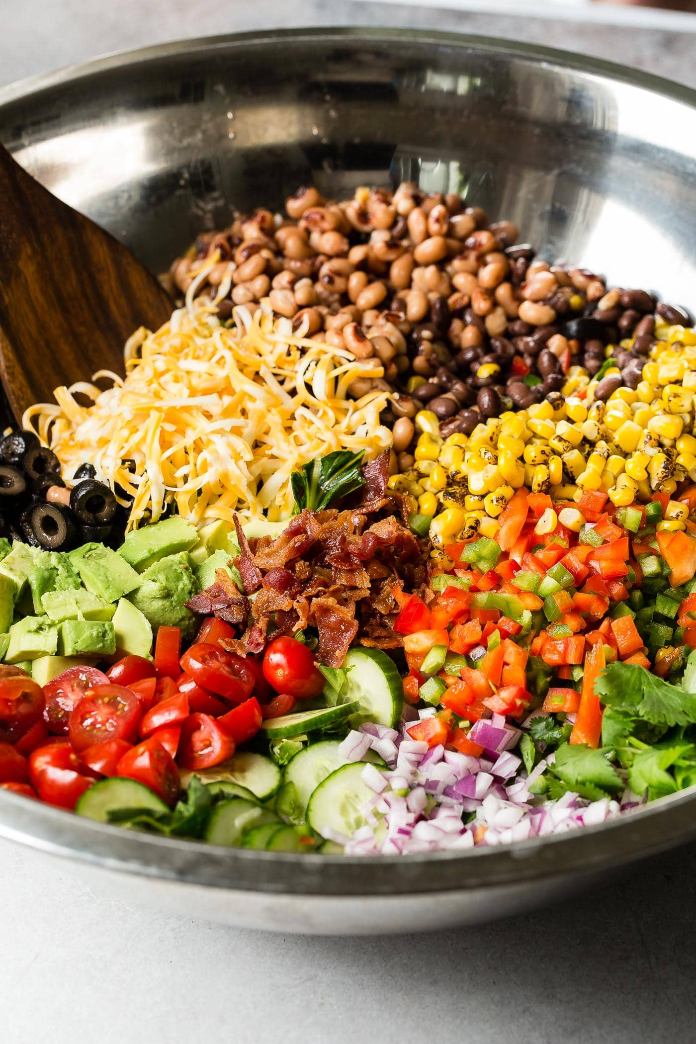 Sections of chopped tomatoes, avocados, red onion, corn, cilantro, beans, shredded cheese, olives, peppers, bacon, and peas in a glass bowl with a wooden spoon.