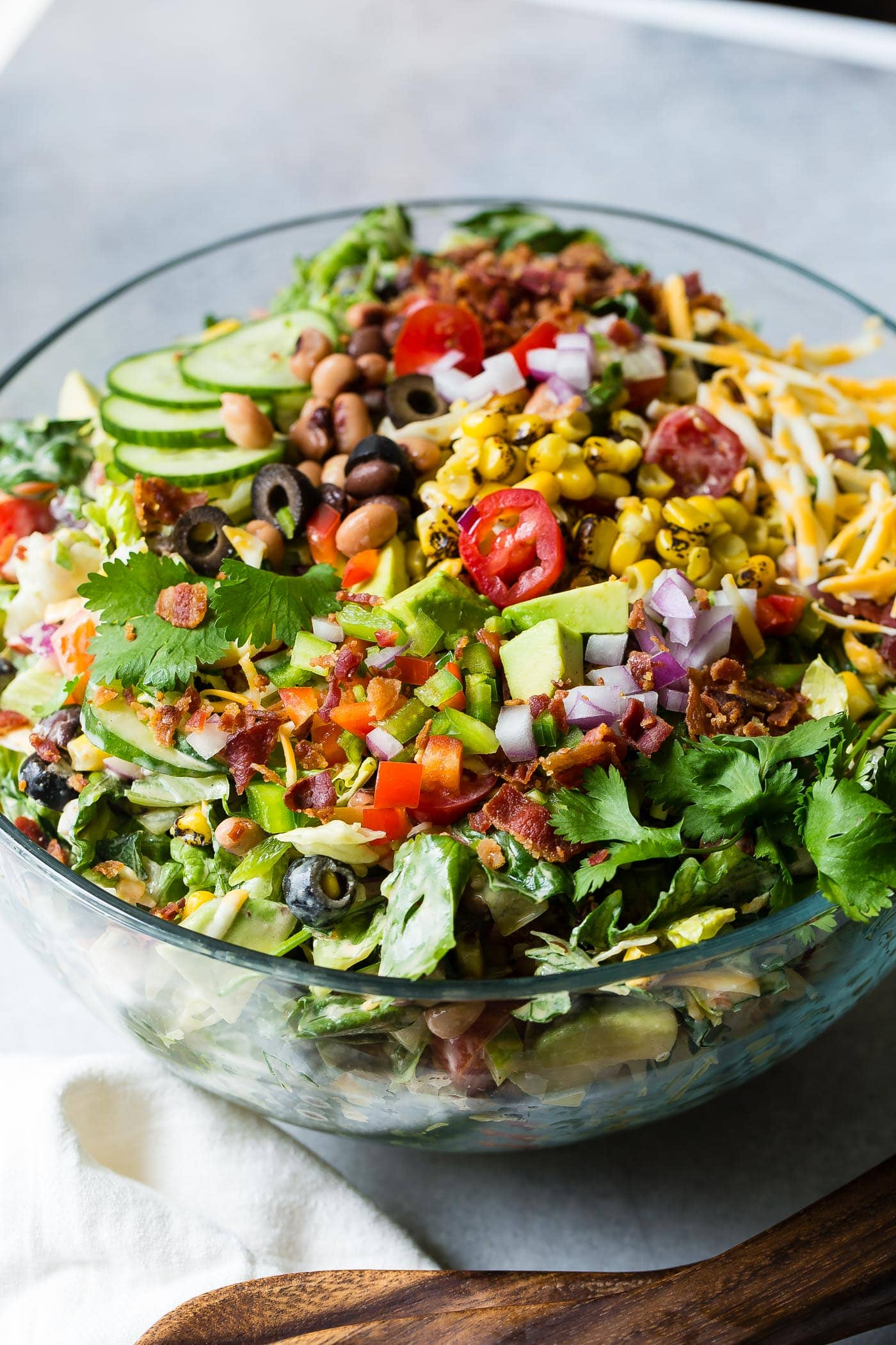 Cowboy salad that is all mixed up and ready to eat. There are sliced cucumbers, chopped tomatoes, chopped avocados, corn, beans, red onions, shredded cheese and green lettuce.