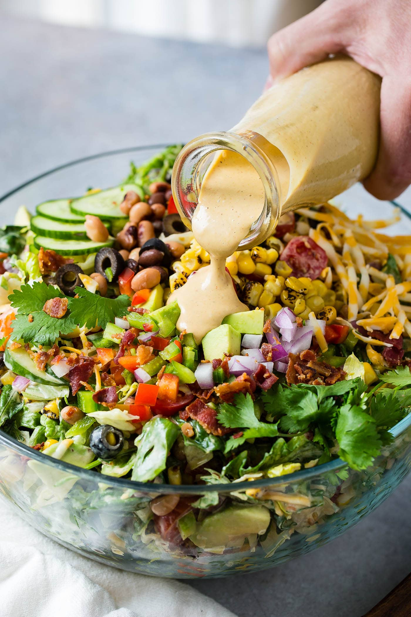 Cowboy salad in a serving bowl. A special dressing is being poured over the chopped onions, tomatoes, bacon, avocados, beans and lettuce.