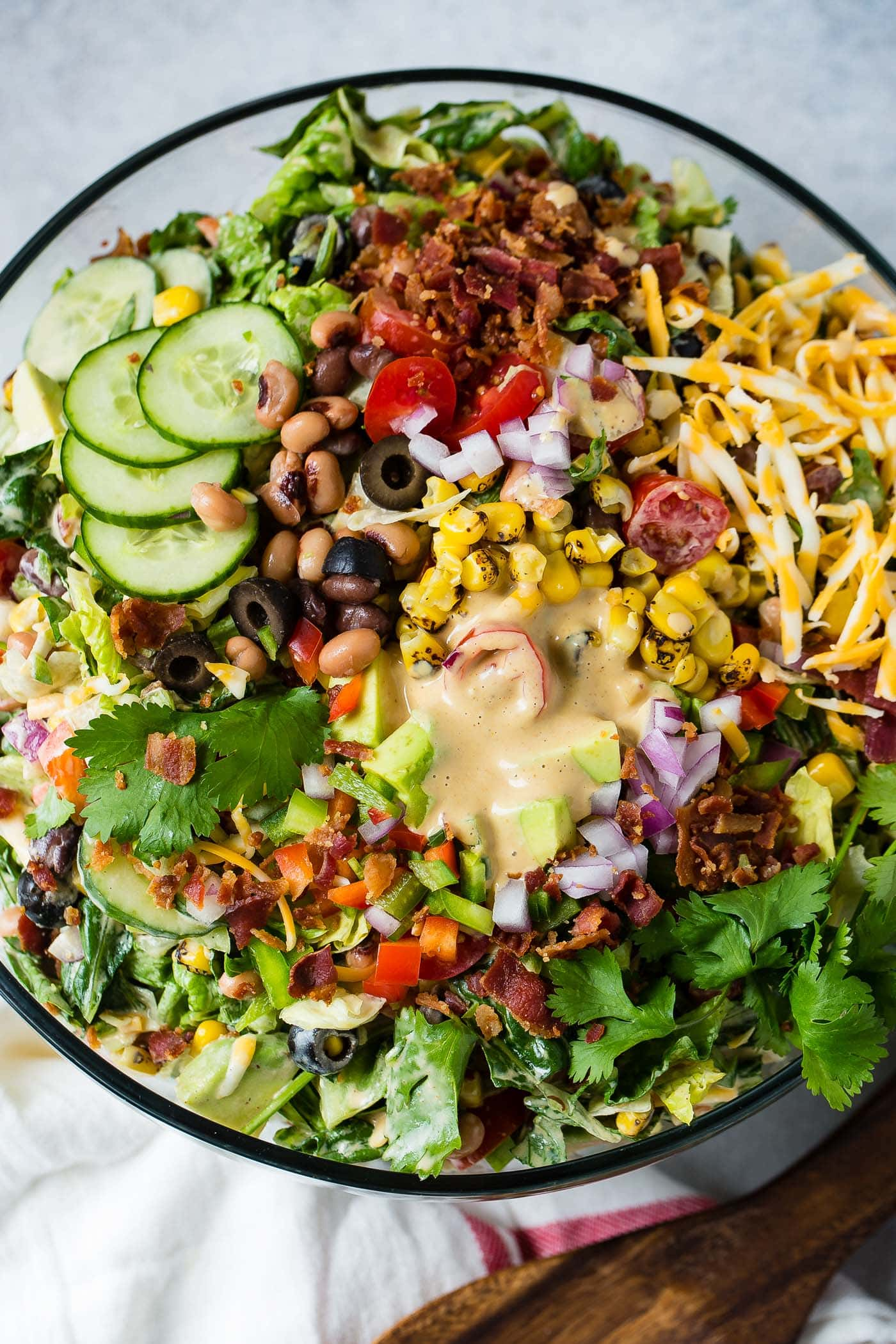 A top view of cowboy salad in a glass serving bowl. There are sliced cucumbers, sliced olives, chopped tomatoes, avocados, lettuce and green onions. It contains corn and beans too and is topped with dressing.