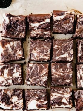 A close up of cheesecake brownies. They are cut into squares and have cheesecake swirled through them.
