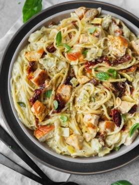 a photo of creamy chicken pasta topped with sun dried tomatoes, golden chicken chunks and fresh basil.