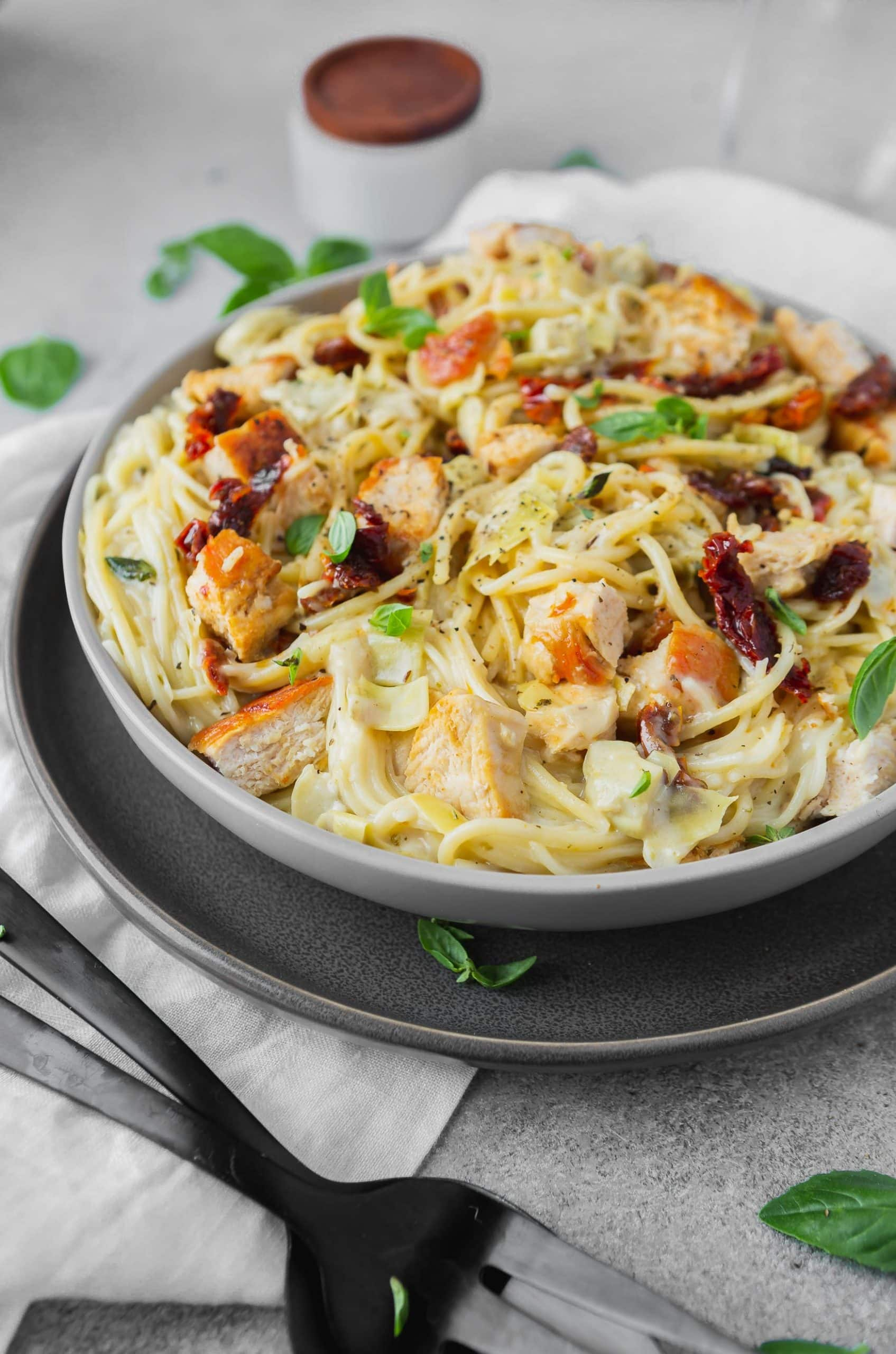 a photo of creamy chicken pasta with sun dried tomatoes and fresh basil on top.