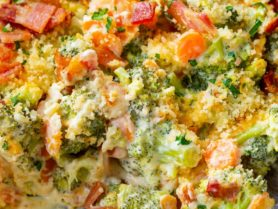 A photo of a cheesy broccoli casserole in a baking dish that is covered in crispy bacon and panko bread crumbs.