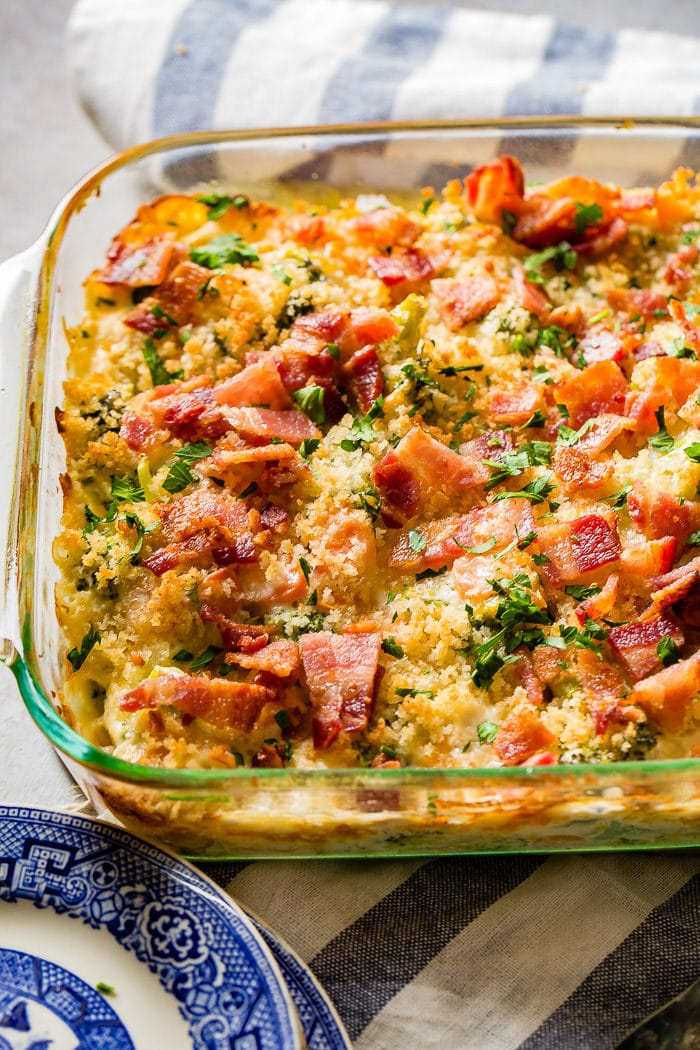 A photo of a cheesy broccoli casserole with crispy bacon and panko bread crumbs on top in a glass baking dish.