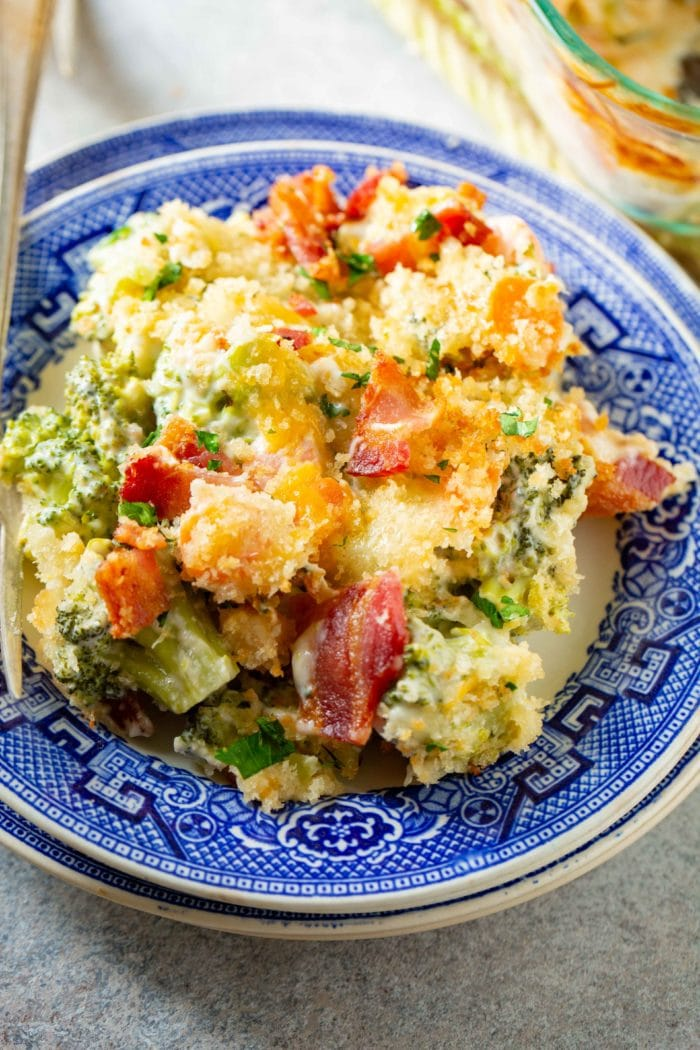 A photo of a serving of broccoli casserole topped with crispy bacon and panko bread crumbs.n a blue plate.