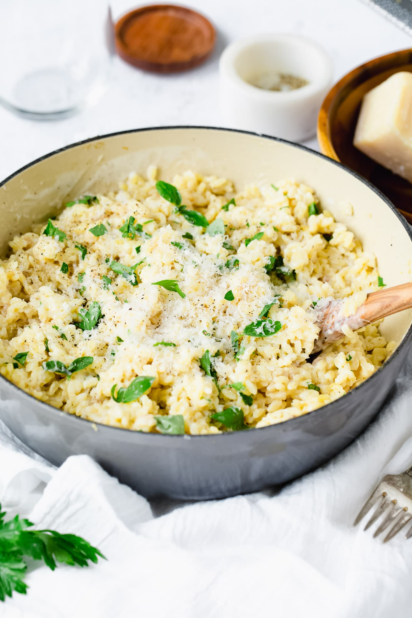 A bowl of creamy garlic parmesan orzo. It has a creamy white sauce and freah thyme leaves over it. There is a fork next to it and small containers of ingredients in the background. The bowl is sitting on a white tea towel.