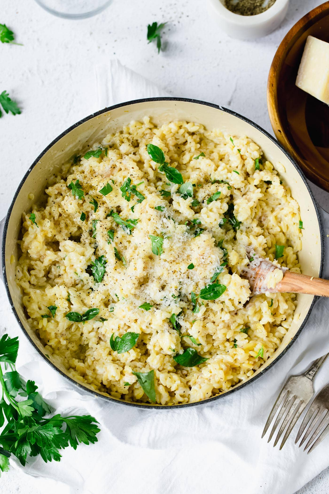 A serving bowl of creamy orzo. There is a wooden spoon in the pasta and the pasta is mixed in a creamy white sauce with fresh thyme leaves. There are fresh thyme leaves and a couple of forks laying next to the bowl.
