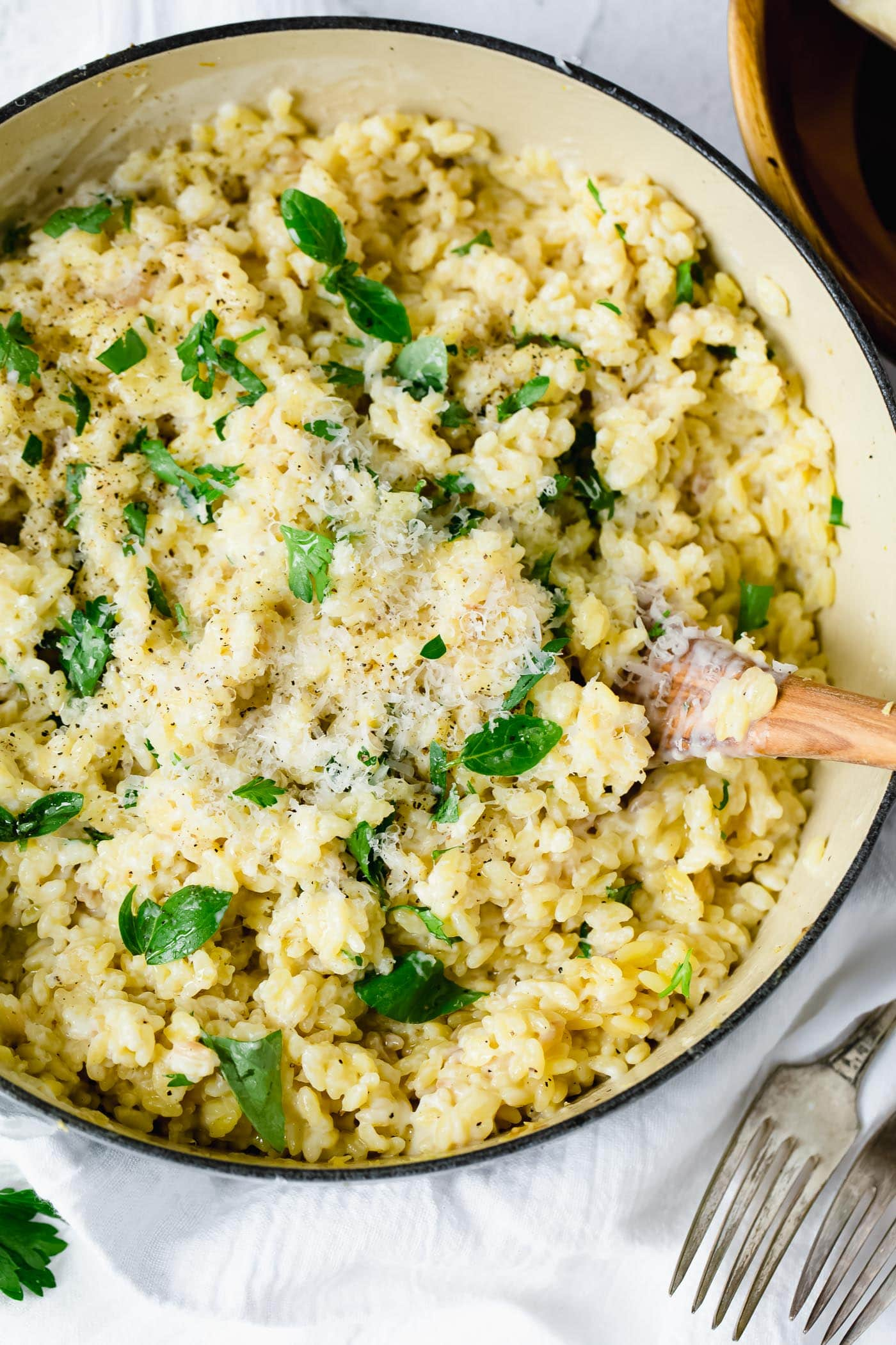 Creamy garlic parmesan orzo in a serving dish. There is a wooden spoon in the pasta. The pasta has been mixed with a creamy white sauce and fresh thyme leaves. Two forks are laying beside the bowl of pasta.