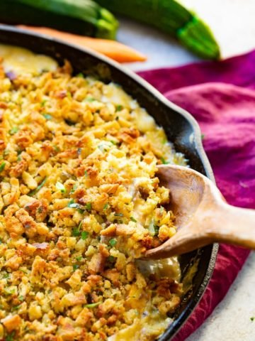 a photo of a cast iron skillet full of a creamy zucchini casserole topped with stuffing being scooped up by a wooden spoon all sitting on a purple cloth napkin on a table with zucchinis and a carrot in the background