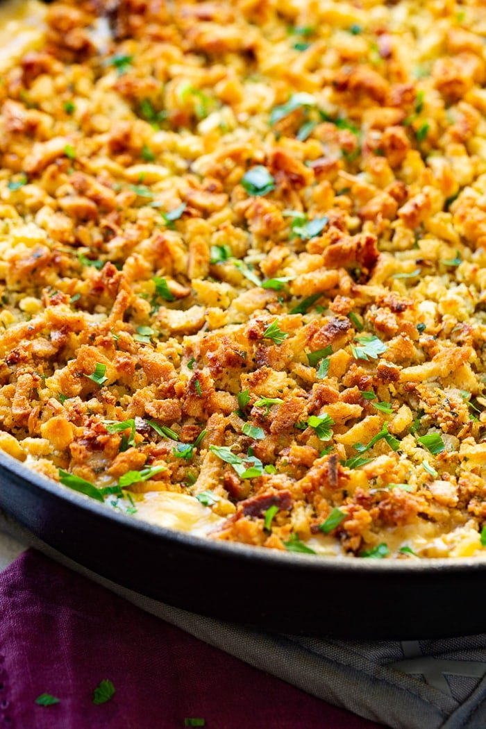 a close up photo of a creamy casserole in a cast iron skillet overed in a toasty stuffing topping