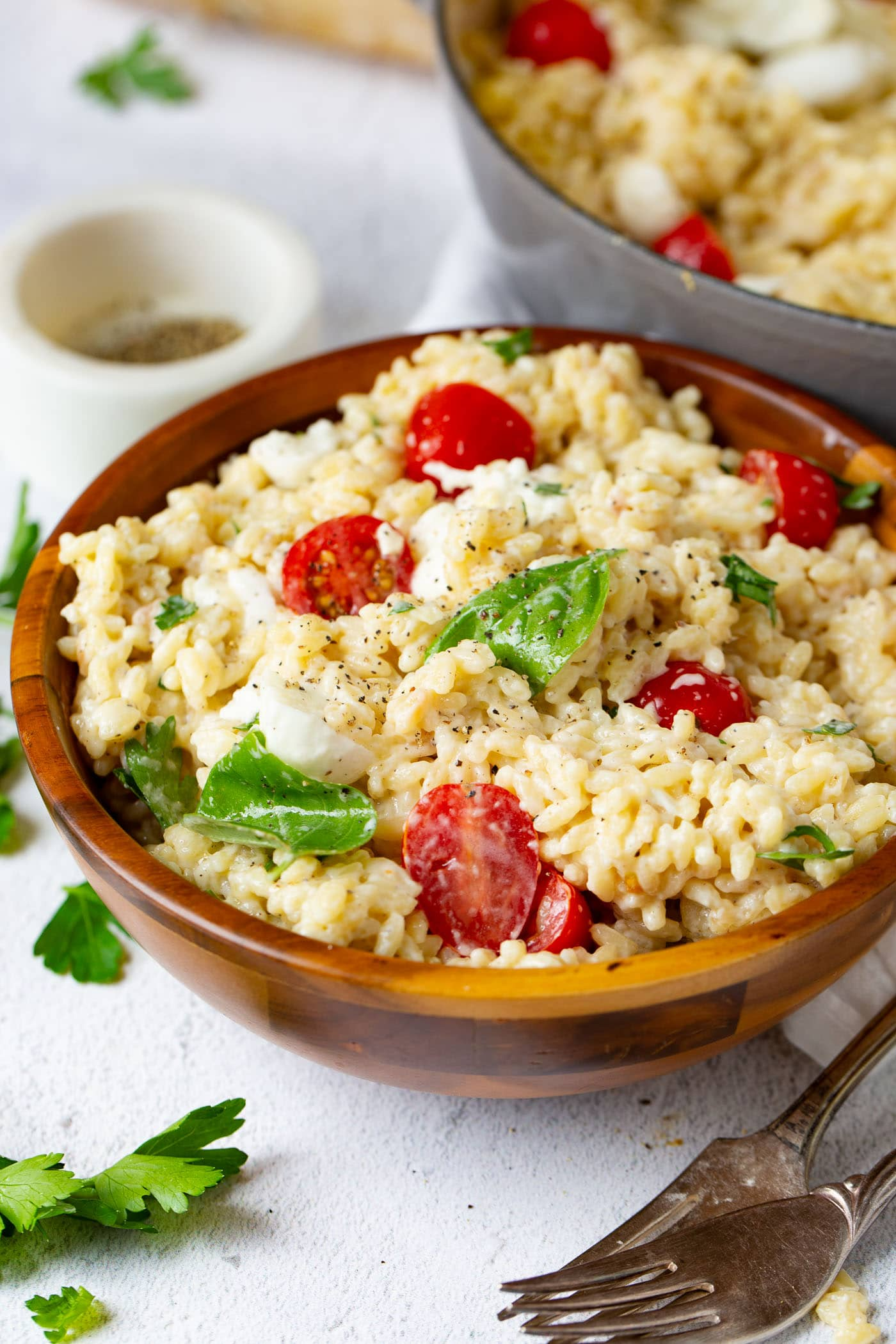 A serving bowl of caprese orzo salad. The salad contains tomatoes, mozzarella chuncks and fresh basil. A few basil leaves, tomatoes and a small container of oil are sitting by the salad.