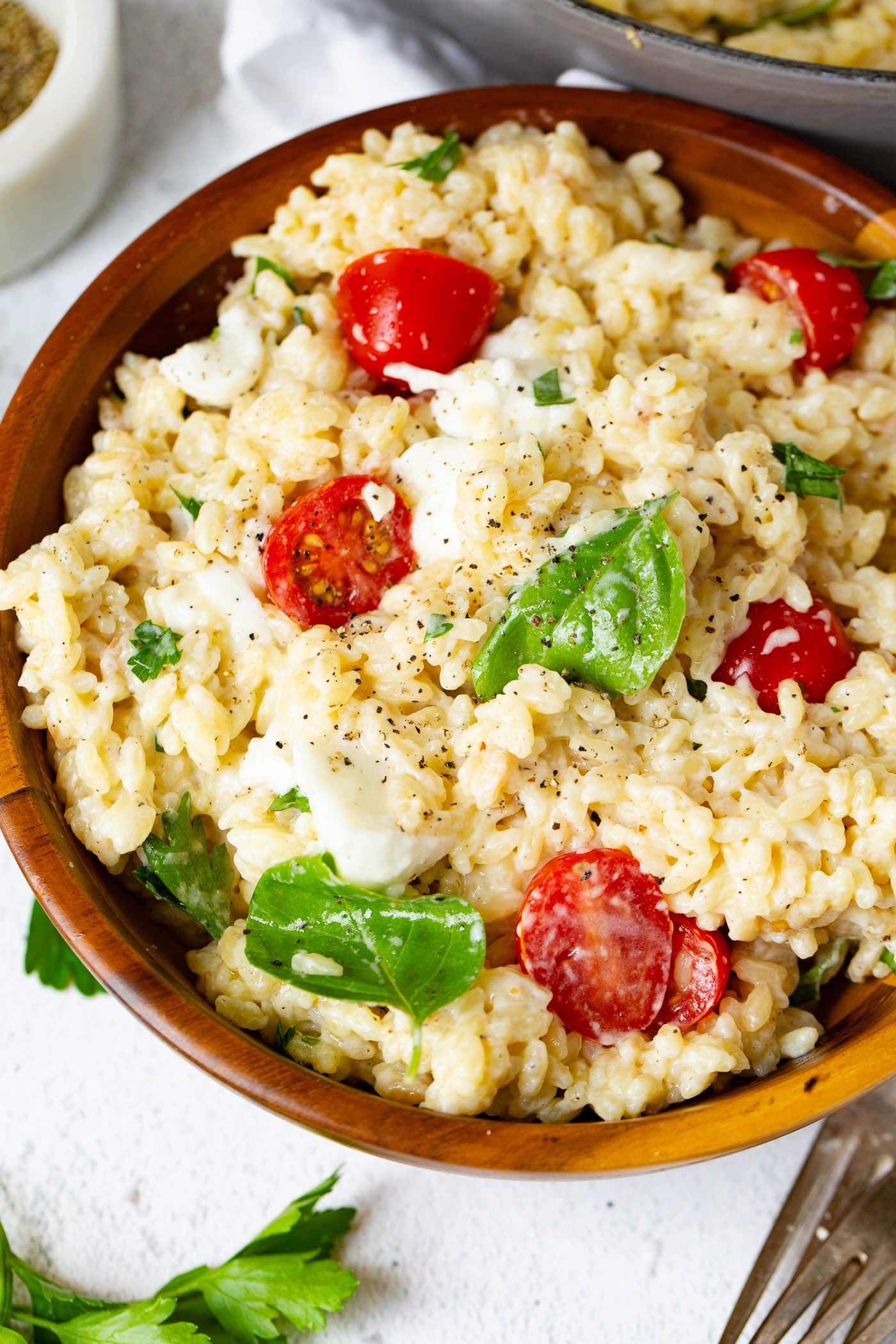 A bowl of caprese orzo salad with fresh tomatoes, mozzarella chunks and fresh basil. A few basil leaves are on the table next to the pasta.