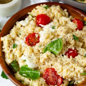 A bowl of caprese orzo salad. The salad has tomatoes, mozzarella chunks and fresh basil leave in it. A container of fresh ground pepper and a few parsley leaves are next to the salad.